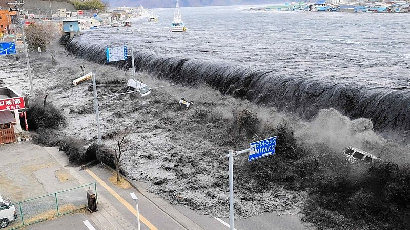 The wave from a tsunami crashes over a street in Miyako City, Iwate Prefecture in northeastern Japan